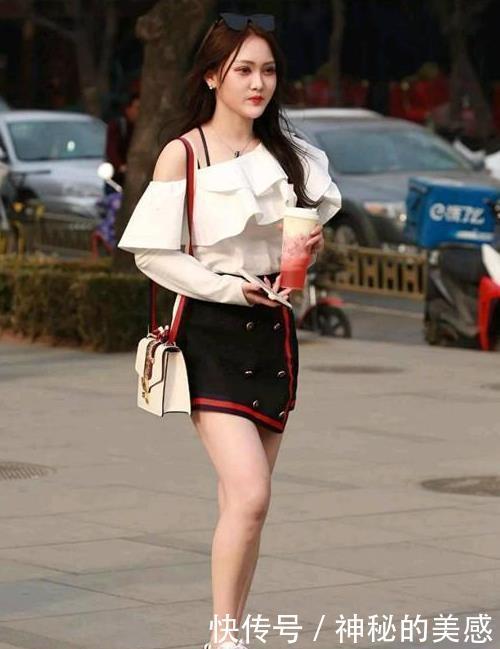 街拍:花颜月貌的美女,一件白色斜肩上衣配黑色短裙,美丽大方
