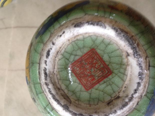 照片中,清乾隆仿哥窑翠青釉地彩绘八仙葫芦瓶是一对臆造的仿品。这对葫芦瓶从形制上与传统葫芦瓶的器型相去甚远,圈口以及上下腹比例严重失调,釉面满贼光,紫口作假明显,铁足忘了做了。釉色深浅不一,开片处未见金丝铁线。彩绘风格现代,人物僵硬,明显是现代印花工艺的产物。胎质松软,底款虽然印的是正确的款识,但是外加双方框纯属画蛇添足。此外,工艺粗糙,做旧手法拙劣等等就不逐一叙述了,关键是,乾隆年间就没有过仿哥窑彩绘葫芦瓶,这完全是作伪者凭空臆造的产物。葫芦瓶因其塑形复杂,制作不易,所以比起其它器型的瓷器来说,葫芦瓶造